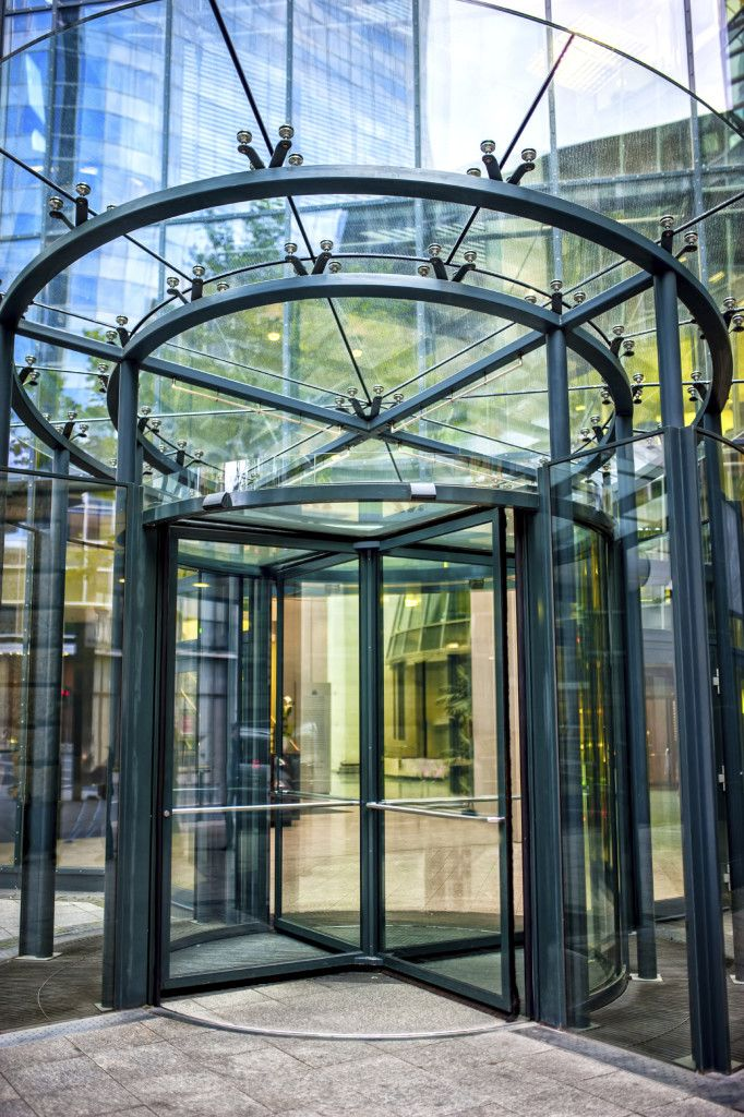 close-up of modern secured glass door at corporate business building. Revolving door at business center or corporate building
