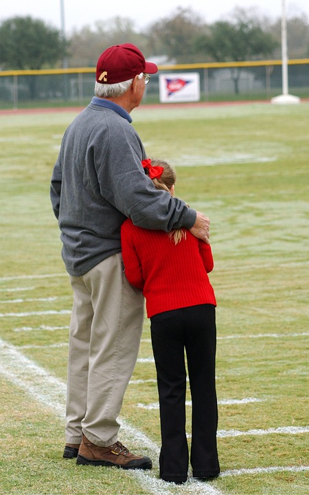 grandfather and granddaughter at football field